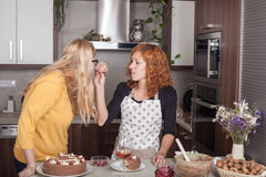 Girlfriends eating and cooking together Royalty Free Stock Image