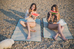 Girlfriends eating watermelon on the beach Royalty Free Stock Photography