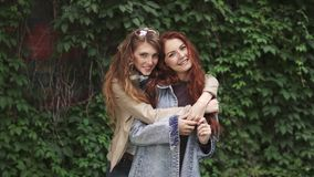 Girlfriends embrace. female friendship. Red-haired girl hugs her best friend from the back. Laughter and fun. 20s. Two redheaded girlfriends goofing around and stock video