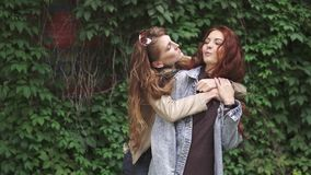 Girlfriends embrace. female friendship. Red-haired girl hugs her best friend from the back. Laughter and fun. 20s. Two redheaded girlfriends goofing around and stock footage