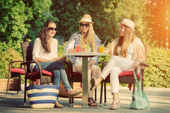 Girlfriends enjoying cocktails in an outdoor cafe, friendship concept. Three attractive girlfriends enjoying cocktails in an outdoor cafe, friendship concept Royalty Free Stock Photo