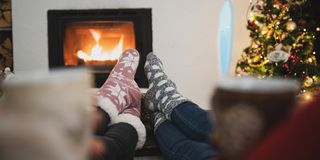 Girlfriends enjoying by the fireplace at Christmas holidays