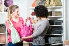 Girlfriends in fashion store buying handbag. Girlfriends in fashion store buying leather handbag Stock Photography