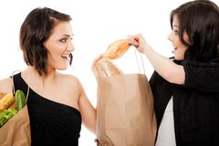 Girlfriends fighting over baguette Royalty Free Stock Images