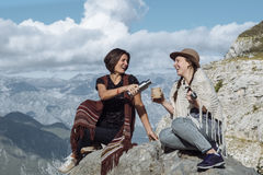 Girlfriends in the folk clothes laughing and having tea on the m Royalty Free Stock Photography