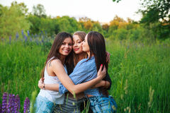 Girlfriends Friendship Happiness Community Concept. Three smiling friends hugging outdoors in the nature. Summertime Royalty Free Stock Image