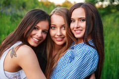 Girlfriends Friendship Happiness Community Concept. Three smiling friends hugging outdoors in the nature. Summertime Stock Images