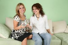 Girlfriends with glasses on sofa Royalty Free Stock Photos