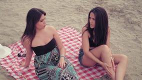 Girlfriends gossip on the beach stock video