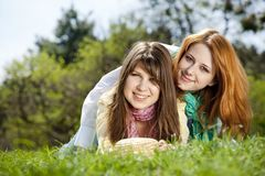 Girlfriends at green grass in the park Royalty Free Stock Image