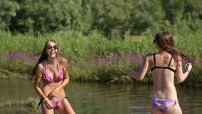 Girlfriends have fun and dancing on the river beach. stock video