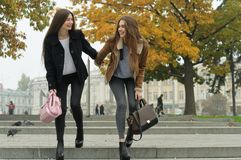 Girlfriends have fun and run down the steps of the sidewalk royalty free stock photo