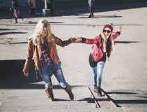 Girlfriends having fun on the stairs. Girlfriends helping eachoder and having fun on the stairs Stock Photo