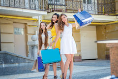 Girlfriends having fun together. Girls holding shopping bags and Royalty Free Stock Photo