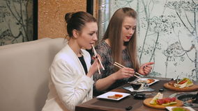 Girlfriends having lunch in a restaurant. Girlfriends having lunch in Japanese restaurant. Cooking on the grill in front of customers stock video footage