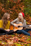 Girlfriends having a nice time with a guitar Royalty Free Stock Images