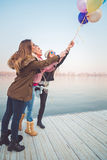 Girlfriends holding bunch of balloons Royalty Free Stock Image