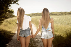 Girlfriends holding hands on a sunny day. summerfeeling Stock Photography