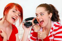 Girlfriends holding headphones and listening music Royalty Free Stock Photography