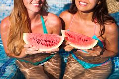 Girlfriends holds half a red watermelon over a blue pool, relax stock images