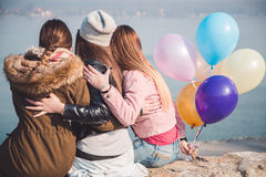Girlfriends hugging on river bank Stock Images