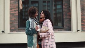 Portrait of two girlfriends against a background of modern architecture. girlfriends embrace. Girlfriends hugging and smiling on the background of modern stock footage