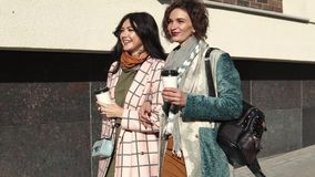 Girlfriends for a walk. two young beautiful women are walking around the city holding coffee. Girlfriends hugging and smiling on the background of modern stock video footage