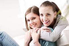 Girlfriends hugging on sofa Stock Photo