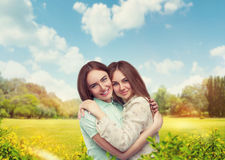 Girlfriends hugs together, nature on background Royalty Free Stock Image