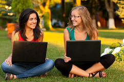 Girlfriends with laptops sitting Stock Photography