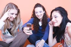 Girlfriends laughing. Three girlfriends laughing, talking and reading a message on the mobile phone stock images