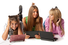 Girlfriends lay with laptops Royalty Free Stock Images