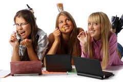 Girlfriends lay with laptops and sugar candies Stock Photography