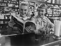 Girlfriends looking at magazine at soda fountain Royalty Free Stock Photography