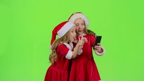 Girlfriends in an embrace photographed on a smartphone. Green screen. Girlfriends in New Year`s costumes in an embarrassment photograph themselves on the stock video