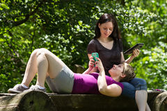 Girlfriends at park using smartphone and tablet, horizontal Stock Photos