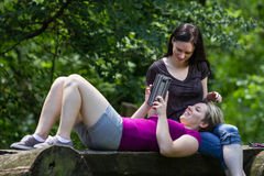 Girlfriends at park using smartphone and tablet, horizontal Royalty Free Stock Images