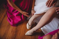 girlfriends in pink dresses, help the bride wear white shoes royalty free stock photography