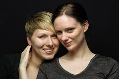 Girlfriends posing against black background, horizontal Royalty Free Stock Images