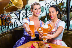 Girlfriends with Pretzel and Beer in Bavarian Inn Stock Photos