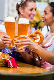 Girlfriends with Pretzel and Beer in Bavarian Inn Stock Images