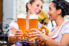 Girlfriends with Pretzel and Beer in Bavarian Inn Stock Photography