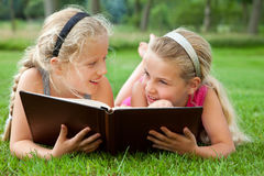 Girlfriends reading a book outdoors Royalty Free Stock Images