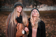 Girlfriends sending kisses. While standing on the leaves Stock Image