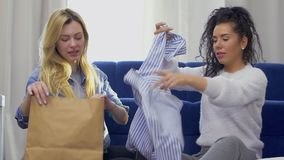 The girlfriends shares their purchases after shopping. Two young girls sits on floor at home after shopping among bags with purchases. The friends discussing the stock video