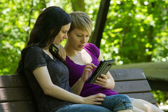 Girlfriends sharing an etablet on park bench, horizontal Stock Photos