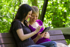 Girlfriends sharing an etablet on park bench, horizontal Stock Images