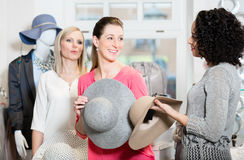 Girlfriends on shopping spree trying ladies hats and other fashion items stock photo
