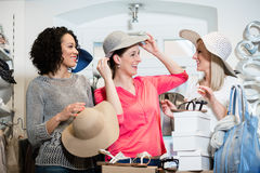 Girlfriends on shopping spree trying ladies hats and other fashion items royalty free stock image