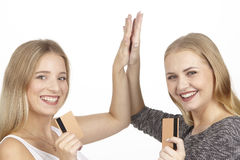 Girlfriends show golden credit cards and make high five Royalty Free Stock Photo